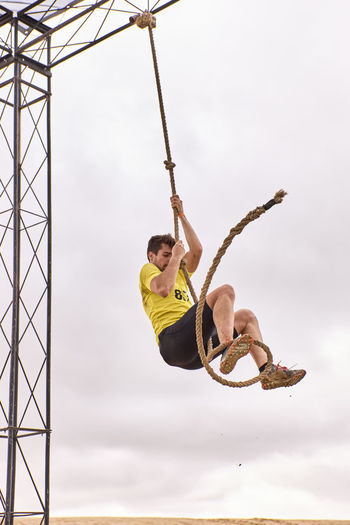 Young man climbing a rope of knots in a spartan race - extreme sport concept