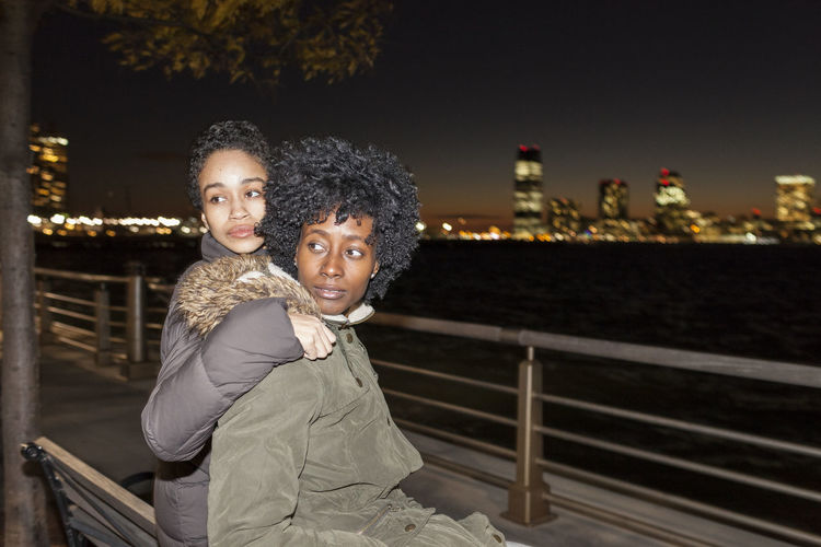 Mother and daughter against railing at night