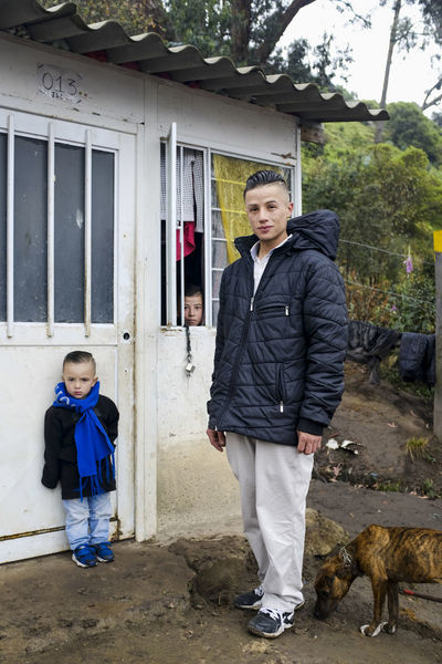 Jeison, with his son Hanner. 22 and 3 years moved into San Germán a couple of months ago with his 17 year old brother, who was visiting that day, can be seen peeking through the window. San Germán is a slum on the outskirts of Bogotá, where vulnerable populations including victims of the armed conflict, ex-guerilla members, single mothers, indigenous and afro communities this neighborhood land is under constant dispute and violence is people here are resilient and determined to stand tall. Colombia Bogota,colombia. Bogotá Bogotá Colombia Family Boys Casual Clothing Inequality Informality Intraurban Displacement Portrait Real People Slum Slum Area Young Family