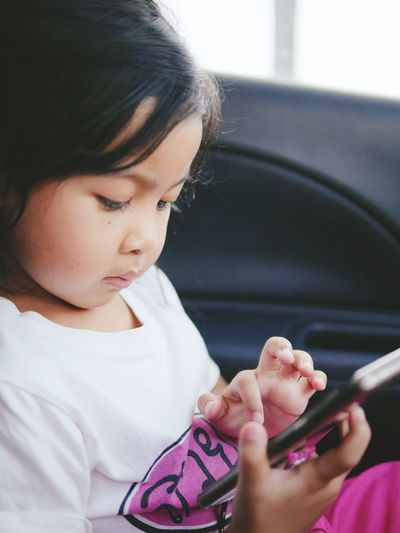 Close-up of girl using phone while sitting in car