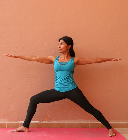 Full length of woman performing yoga while standing against orange wall