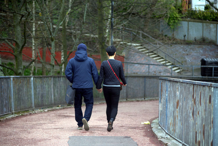 Rear View Of Couple Holding Hands While Walking On Footpath