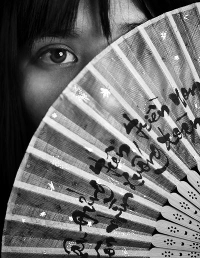 Close-up portrait of woman hiding face behind folding fan