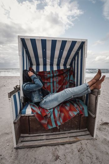 Sky Cloud - Sky Nature Striped One Person Beach Land Day Real People Leisure Activity Full Length Relaxation Sitting Wood - Material Water Lifestyles Outdoors Sea Casual Clothing