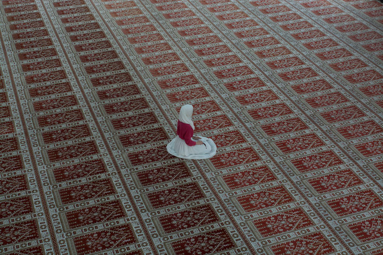 High Angle View Of Woman Praying In Mosque