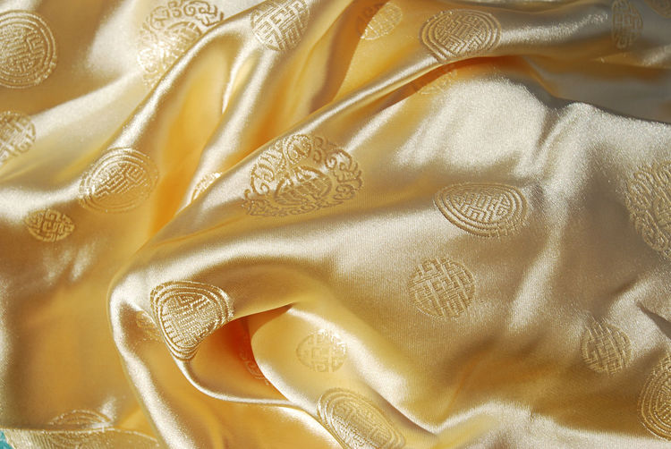 Asian yellow satin fabric. Close-up Crumpled Fabric Material Pattern Satin Shiny Silk Textile Yellow