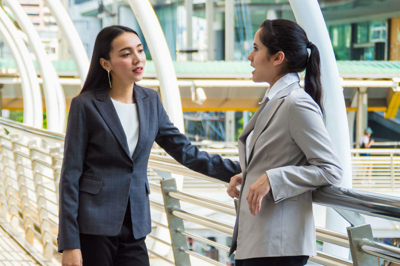 Young businessmen meeting outside the business district. Adults American Asian  Associates Attractive Background Banner Briefing Business Businessman Caucasian Cheerful Collaborations Communication Confidence  Contact Cooperation Coworkers Discussing Discussion Elegant European  Experienced Female Formal Friends Group Image Joy Lady Lifestyle Male Man Meeting Operation Outdoors People Photo Planning Positive Pretty Professional Smiling Solutions Successful Team Urban Woman Work Young