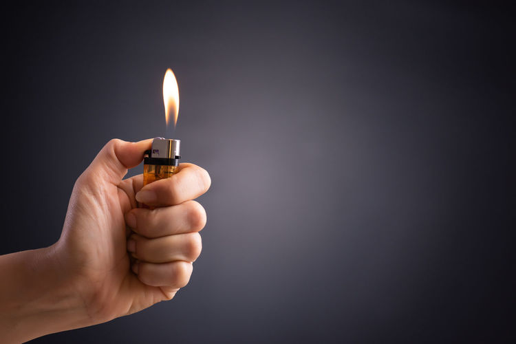 Close-up of hand holding cigarette lighter against gray background