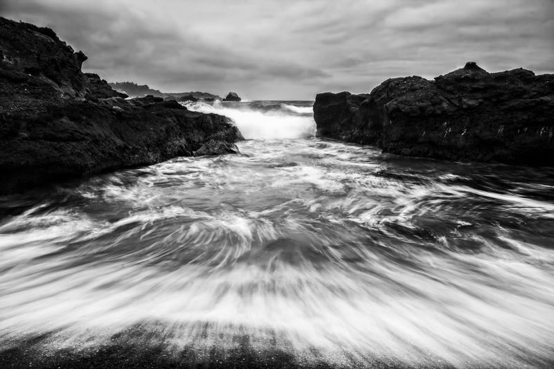 Black and white dramatic seascape with water in motion against rocky shore. California Park State Reserve Point Lobos Carmel Coast Nature Rocks Shore Rock Stormy Storm Formation Seascape Travel Surf Texture Surge Beautiful Beauty Water Powerful Unique Cool Fresh Ocean Sea Conceptual Shape Spray Motion Movement Abstract View Shapes Weather Season  Background Coastal Power Black White Drama Dramatic Scenics - Nature Beauty In Nature Wave Blurred Motion Flowing Water