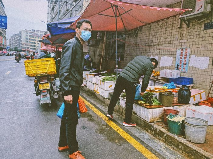 Man standing on street in city during rainy season