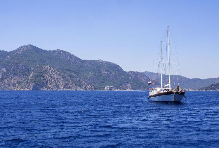 Yacht sailing on aegean sea against clear blue sky