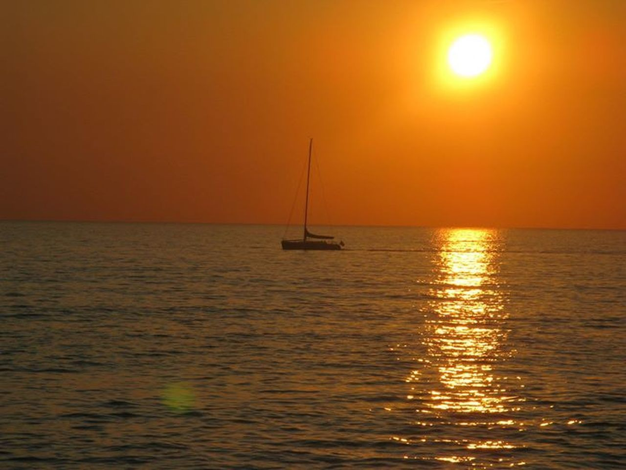 sea, sunset, sailboat, reflection, sun, horizon over water, water, scenics, tranquil scene, yacht, dramatic sky, nautical vessel, tranquility, idyllic, sailing, beauty in nature, vacations, sky, nature, sunlight, mast, sailing ship, no people, horizon, outdoors, travel destinations, beach, yachting, day