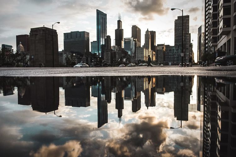 Skyscrapers in city against cloudy sky