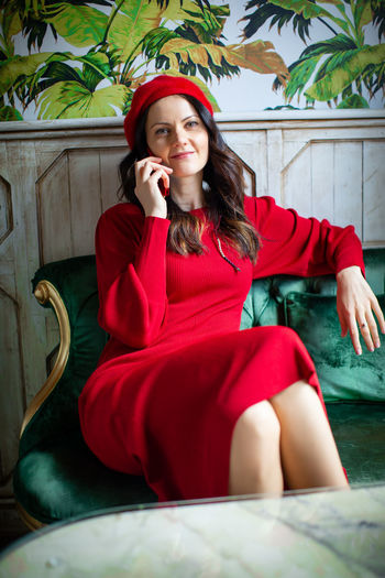 Sitting Red One Person Front View Technology Real People Leisure Activity Telephone Sofa Communication Adult Young Adult Using Phone Women Furniture Indoors  Mobile Phone Clothing Lifestyles Wireless Technology Hair Hairstyle Beautiful Woman Speaking On The Phone