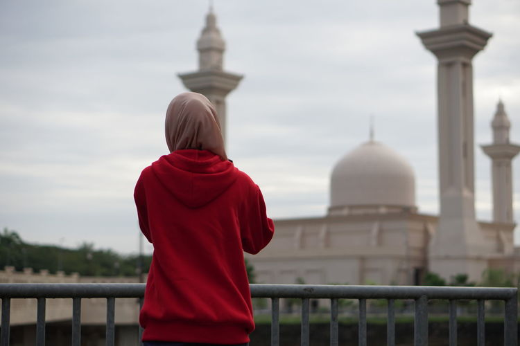 Rear View Of Woman Standing Against Mosque