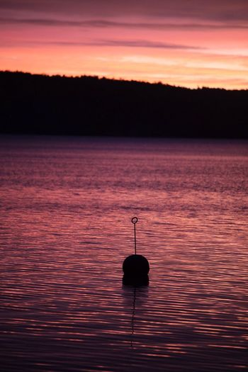 Silhouette boat in water against sky during sunset
