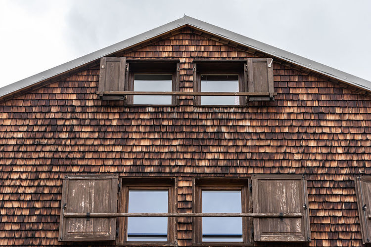 Weathered and faded wooden shingles - the facade of an alpine house. open windows and shutters.