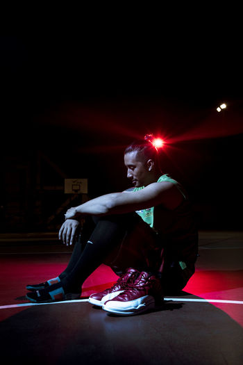 Portrait of Basketball player with Basketball shoes After The Game  Basketball Basketball Court Casual Clothing Dark Flash Light Jordan Leisure Activity Lifestyles Man Night Photography Night Portrait Person Portrait Portrait Of Player Red Red Rest Shoe Shoes Off Sitting Sitting Thinking Young Adult