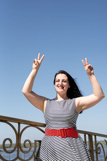 Happiness concept. beautiful young woman opened her hands at the blue sky showing peace gesture