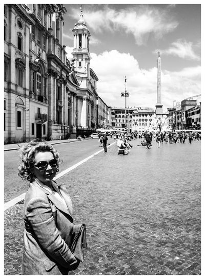Woman standing in city against sky