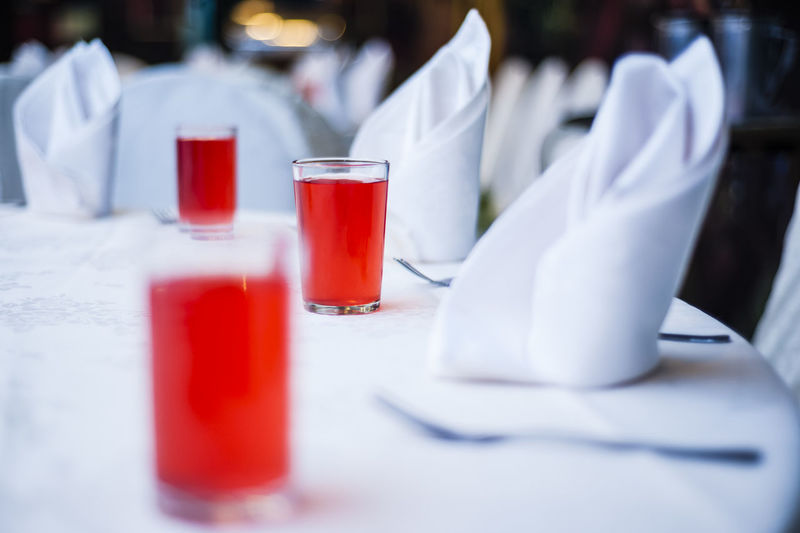 Red Drink In Glasses By Napkins Arranged In Table At Restaurant