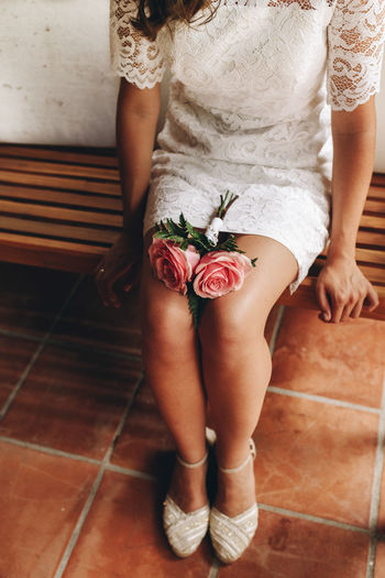 Low section of bride with flower sitting on bench