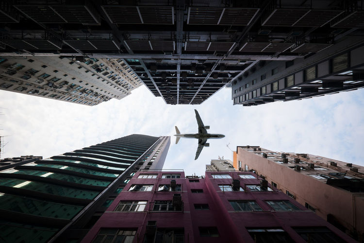 Built Structure Architecture Low Angle View Building Exterior Building Sky City Day Air Vehicle Flying Outdoors Tall - High No People Nature Airplane Office Building Exterior Cloud - Sky Directly Below Transportation Tower Skyscraper