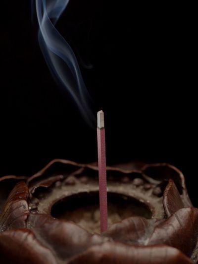 Close-Up Of Incense Stick Emitting Smoke Against Black Background
