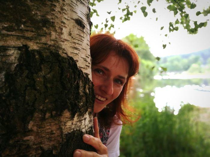 Portrait of young woman against tree trunk
