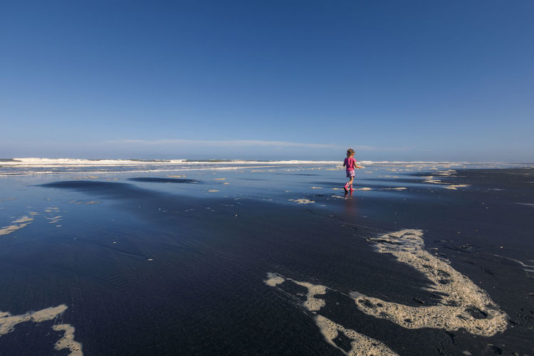 Rear view of girl walking at beach against blue sky