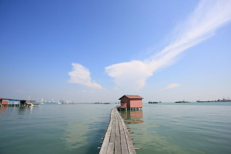 Scenic view of pier by building against sky