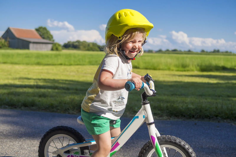 Girl with bicycle on grassy field