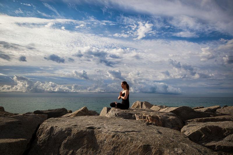 Man sitting on rock by sea against sky