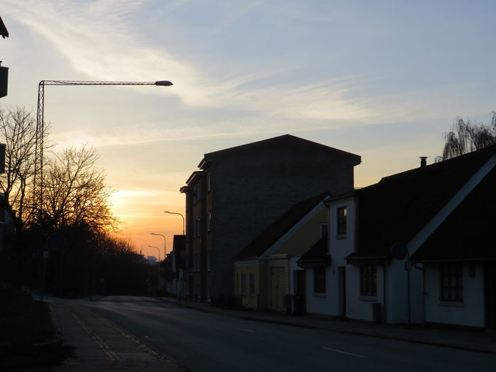 Road by silhouette buildings against sky during sunset