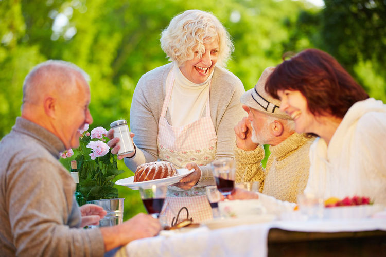 Cheerful Friends Having Food At Table In Park