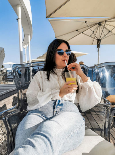 Portrait of beautiful and stylish young woman drinking cold drink in bar on sea shore.