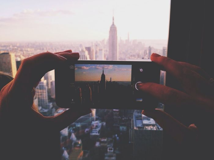 Cropped Image Of Person Photographing Empire State Building Through Smart Phone