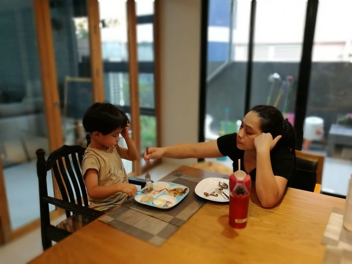 Mother feeding son while sitting at dining table