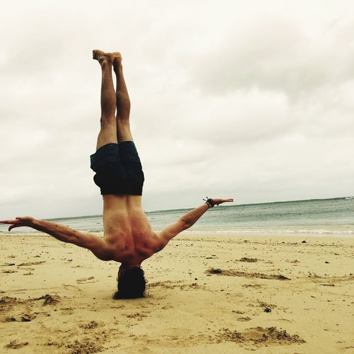 Shirtless Man Doing Headstand At Beach Against Cloudy Sky