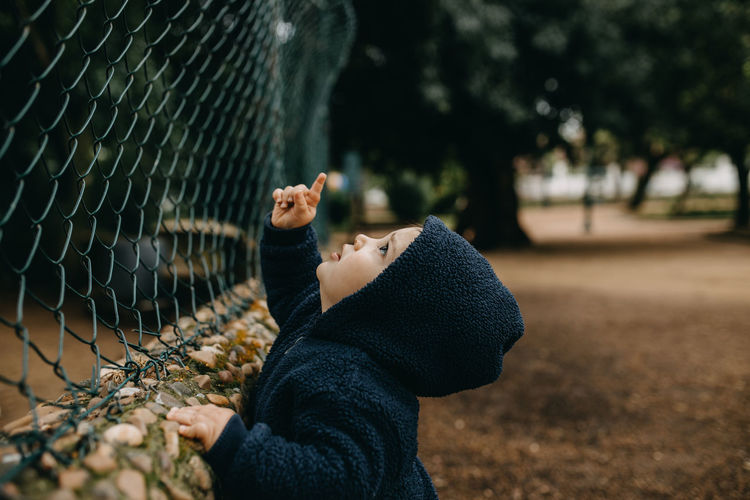 Side view of boy playing with chainlink fence