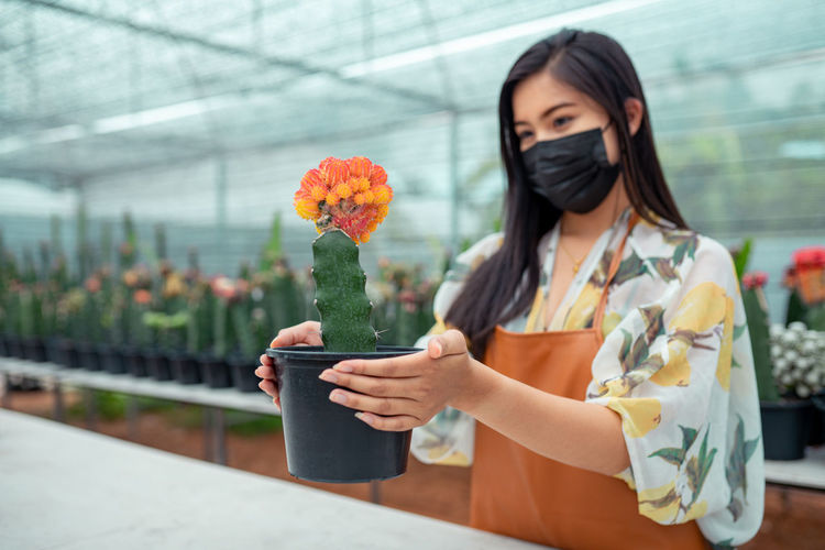 Woman holding flower standing in greenhouse