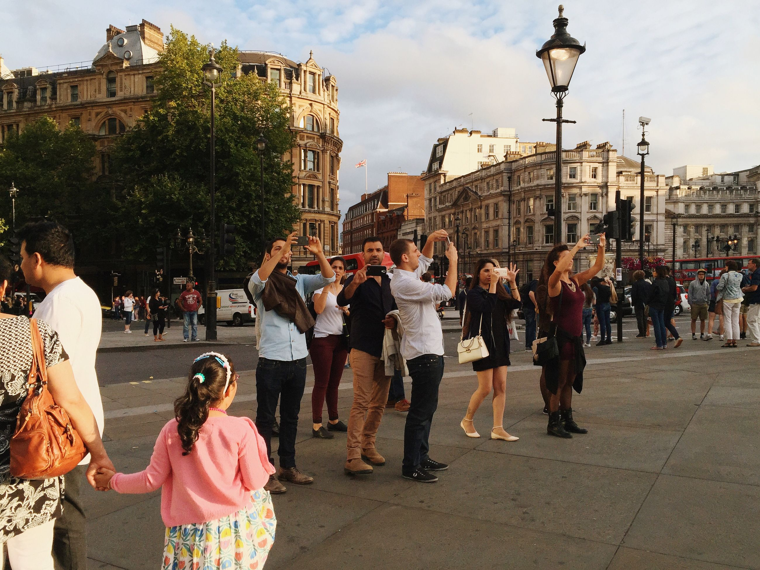 large group of people, building exterior, architecture, built structure, person, lifestyles, men, city, street, leisure activity, city life, mixed age range, walking, crowd, sky, tree, town square, tourist, city street