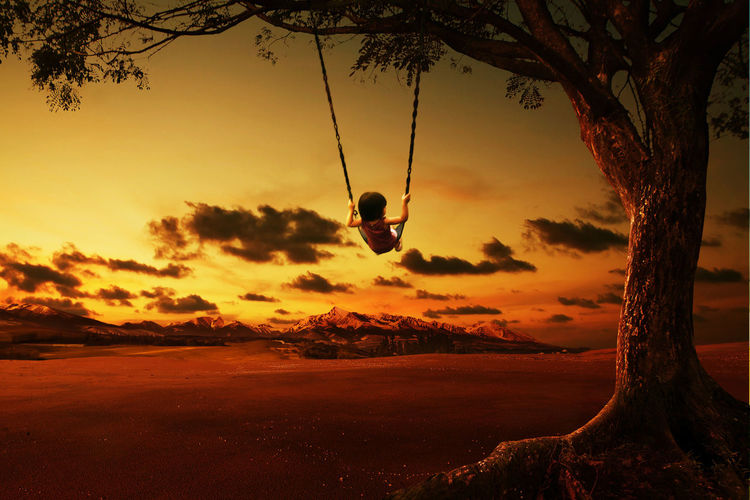 Rear view of girl swinging over land against sky during sunset