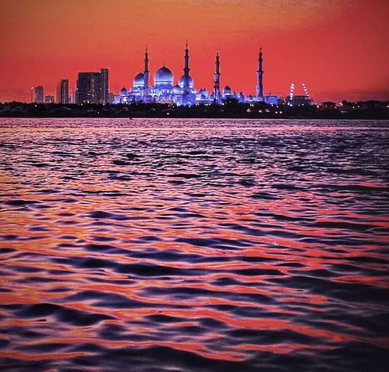 Beautiful Sunset across the water to Sheikh Zayed Mosque in Abu Dhabi Abu Dhabi Abu Dhabi Grand Mosque Beautiful Architecture Mosque Sunset Night Sea