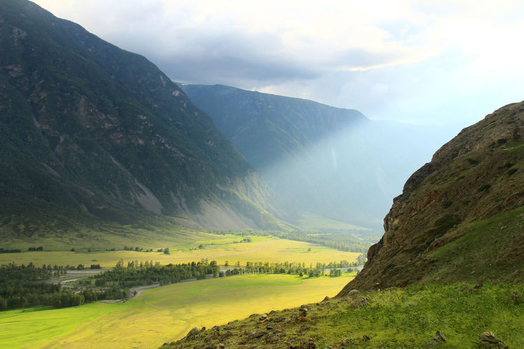 A ray of light in a high-altitude green valley with huge mountains