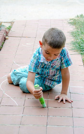 an active little boy enjoys drawing outdoors on a beautiful summer dayKids Summertime Active Kids Art Boys Childhood Creative Day Drawing Kids Having Fun One Person Outdoors People Playing Outdoors Real People Sidewalk Chalk
