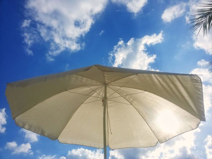 The Sun shines through a Sunshade Summer Tropical Tourism Outdoor Silhouette Cloud - Sky Parasol Low Angle View Blue Close-up Travel Enjoying Life Colors No People Sun Day Palm Relaxing Holidays
