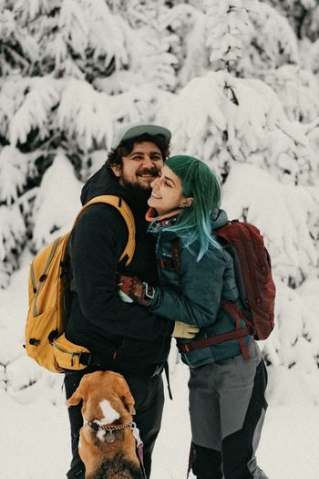 Couple in love with dog on snow