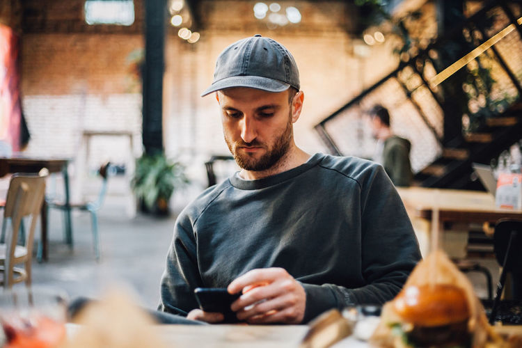 Portrait of young man using mobile phone in cafe
