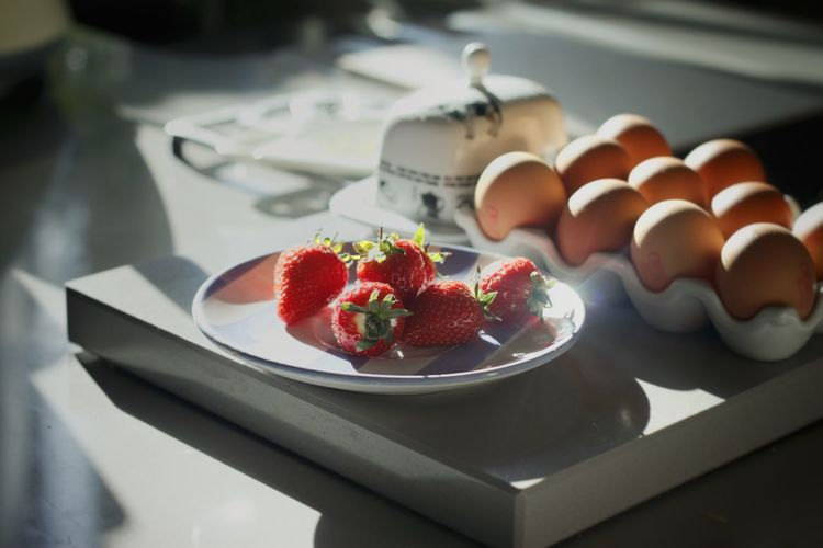 Sunlight falling on eggs in carton by strawberries at table